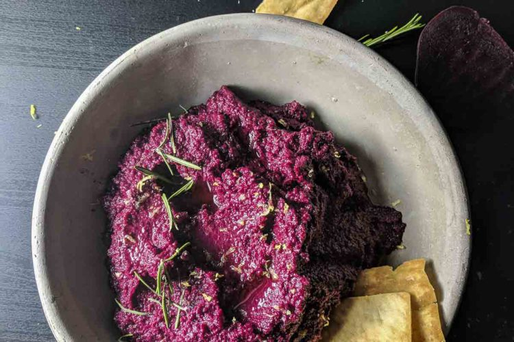 Overview of Beet Hummus on bowl with pita chips